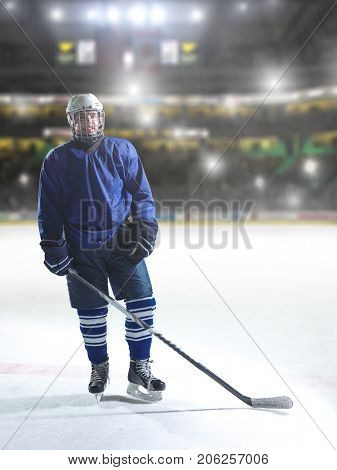 young ice hockey player portrait on training in front of big modern hoykey arena with lights and flares