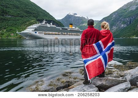 Sea cruise in Norway. Couple of travelers with a Norwegian flag look at the Cruise liner. Fjord Geirangerfjord near Geiranger city