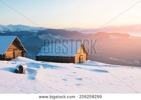 Winter landscape in a mountain village. Wooden houses and huts in the snow