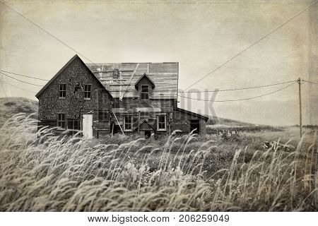 Derelict house in a middle of a field in sepia with texture to look like an used picture