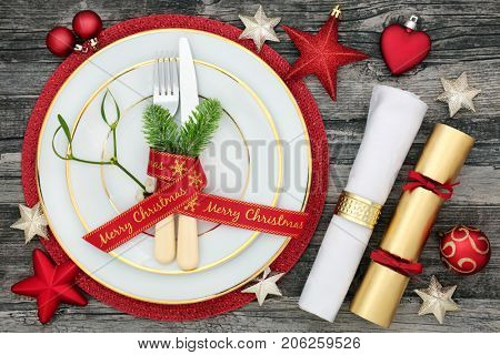Christmas table place setting with dinner plates, cutlery with fir and ribbon, napkin, cracker and bauble decorations  on distressed wood background.