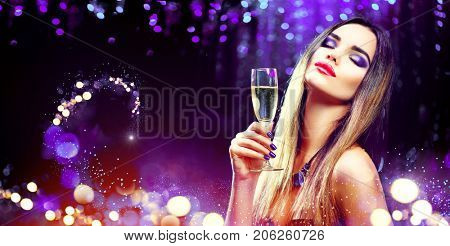 Sexy model girl with glass of champagne at party, drinking champagne over holiday glowing blue background. Beauty woman with perfect fashion makeup. Christmas and New Year holiday celebration