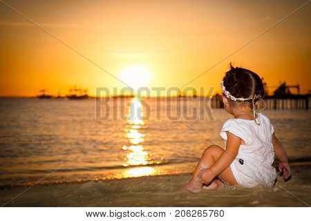 BORACAY, PHILIPHINES- MARCH 17, 2017: Baby gazing on the sunset at White beach ,  Boracay island on March 17, 2017. Philiphines.