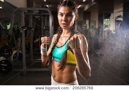 Physically strong young female with pigtails looking at camera during training in gym