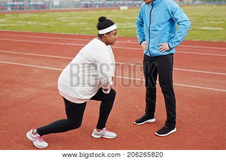 Young plump woman in activewear bending her knees during physical exercise with her trainer standing in front