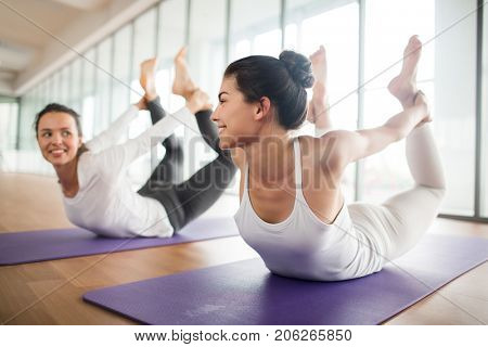 Active and flexible girls lying on bellies and holding legs in hands while practicing yoga on mats