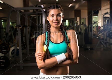 Young sweaty girl with pigtails looking at camaera in gym with her arms crossed on chest