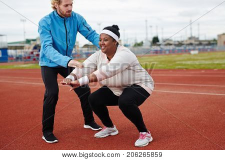 Happy young oversized female doing squat exercise with help of individual sport trainer