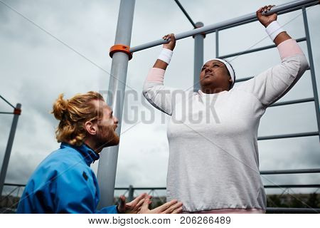 Young trainer encouraging plump female to try harder in doing pull-ups on bar