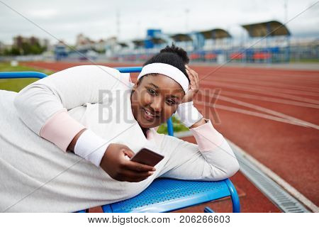 Happy plus-size African-american girl in white sweatshirt, wristbands and headband lying on bench at stadium and texting in smartphone