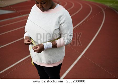 Chubby woman in sportswear measuring her waist after hard training on stadium