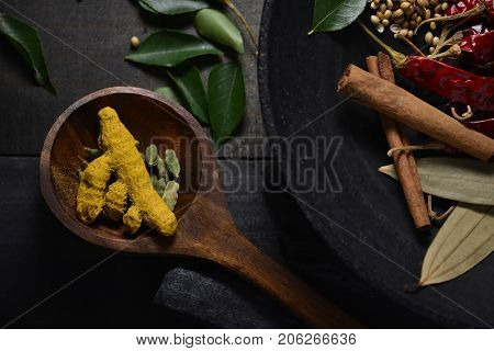 Whole turmeric roots and green cardamom pods placed in a wooden spoon along with whole Indian mixed spices.