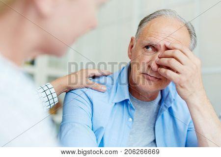 Worried senior man looking at his friend or wife reassuring him
