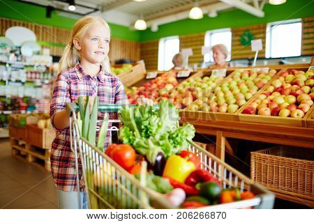 Cute little girl pushing shopping cart with fresh vegetables in supermarket