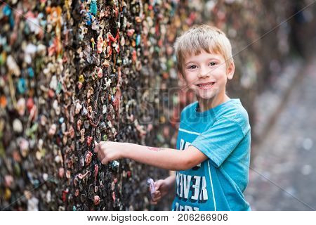 Boy putting gum on the wall in bubble gum alley