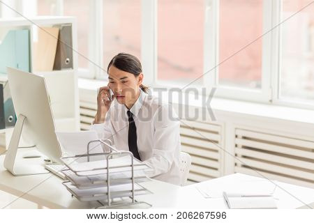 Handsome Asian white collar worker sitting in front of computer and discussing order details with client on mobile phone, interior of spacious office with panoramic windows on background