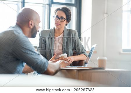 Serious woman listening to co-worker explaining new online business trends poster