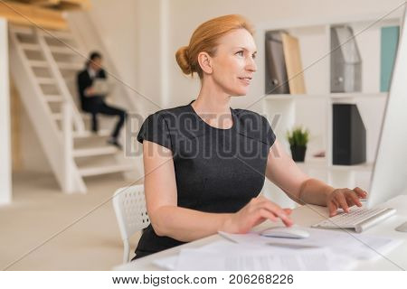 Profile view of talented middle-aged interior designer sitting in front of computer and working on promising project, interior of modern open plan office on background