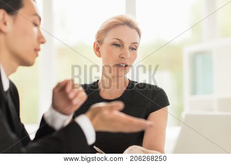 Attractive middle-aged white collar worker and her Asian colleague gathered together at boardroom and brainstorming on start-up project, blurred background