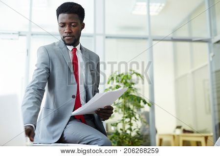 Handsome Africa American white collar worker wearing stylish suit checking business emails on laptop while working at spacious office