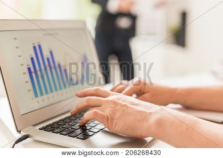 Close-up shot of unrecognizable financial manager sitting at office desk and analyzing statistics with help of laptop, blurred background