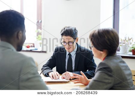 Group of hard-working white collar workers analyzing results of accomplished work while having working meeting at spacious boardroom