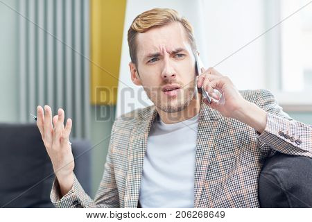 Annoyed young entrepreneur gesticulating and looking away with concentration while having tense telephone conversation with business partner