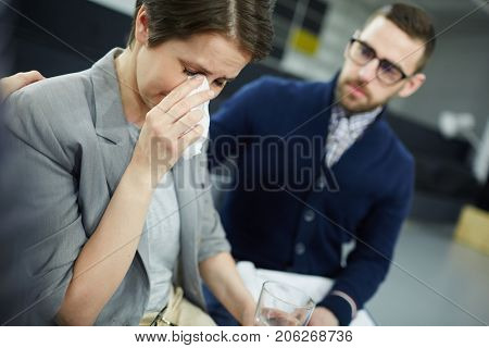 Helpful man expressing sympathy to crying female wiping her tears with handkerchief