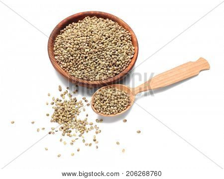 Bowl and spoon with hemp seeds on white background