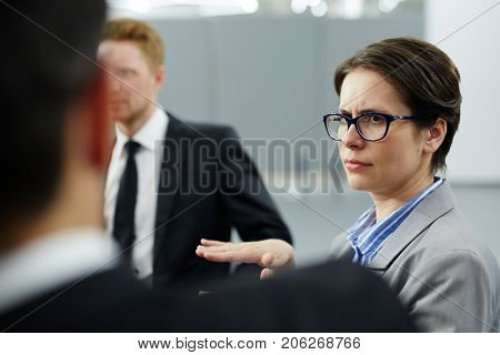 Skeptical businesswoman in eyeglasses expressing disagreement with colleague during discussion