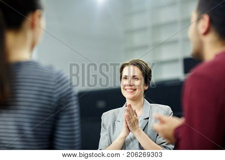 Happy middle-aged businesswoman with her palms put together listening to co-worker or subordinate