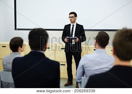 Young speaker in suit standing by whiteboard and making report at business training for attendants