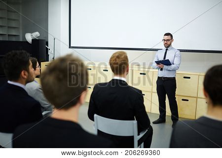 Confident speaker listening to feedback of audience after lecture or master-class