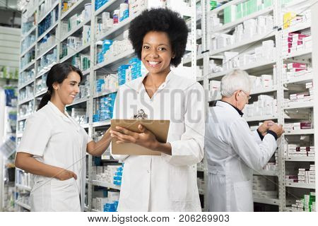 Female Chemist Writing On Clipboard While Colleagues Counting St
