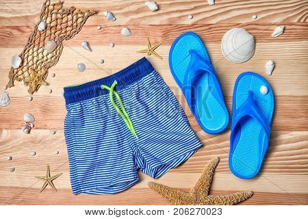 Boy's swimming trunks and flip flops on wooden background