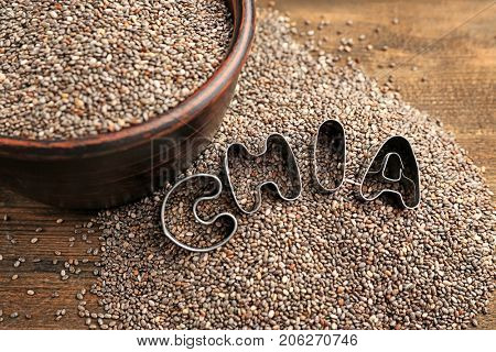 Composition with chia seeds in bowl and metal letters on table