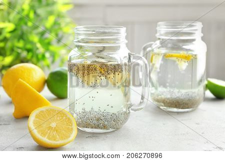Mason jars with chia seeds, lemon and water on kitchen table