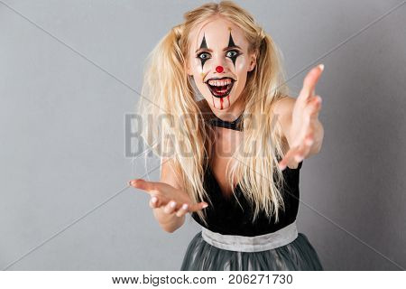 Happy blonde woman in halloween make up extends her hands and looking at the camera with open mouth over gray background