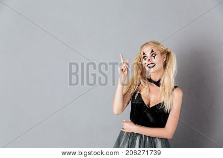 Smiling blonde woman in halloween make-up pointing and looking up over gray background