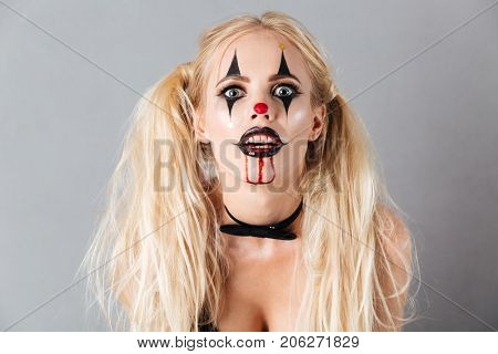 Close up portrait of mystical blonde woman in halloween make up looking at the camera