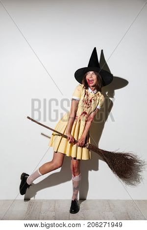Full length image of crazy woman in halloween costume posing with broom and looking away over white background