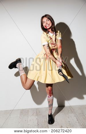 Full length image of happy zombie woman in dress attacking with an axe and looking at the camera over white background