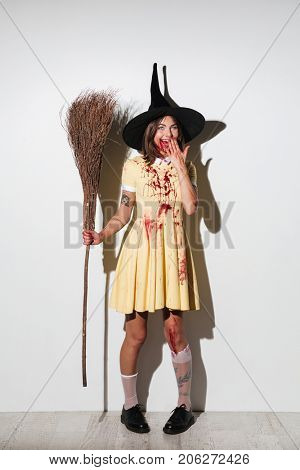 Full length image of happy woman in halloween costume holding broom and covering her mouth over white background