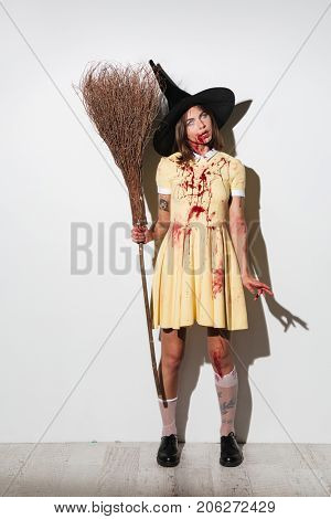 Full length image of frightening woman in halloween costume holding broom and looking at the camera over white background