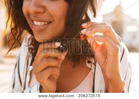 Cropped picture of happy african woman fastens her moto helmet outdoors