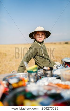Adorable little girl in Kenya safari enjoying bush breakfast