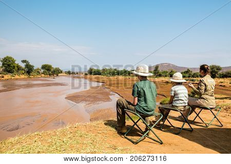 Family of mother and kids on African safari vacation enjoying Ewaso Nyiro River views in Samburu Kenya