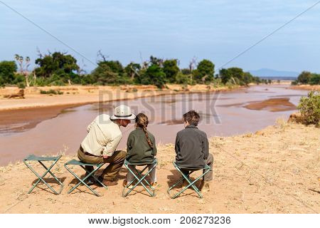 Family of father and kids on African safari vacation enjoying Ewaso Nyiro River views in Samburu Kenya