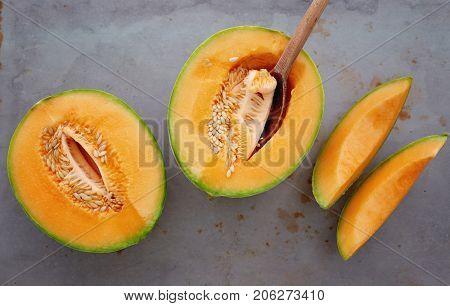 Fresh cantaloupe cut into pieces. Half cut of ripe cantaloupe melon with spoon.