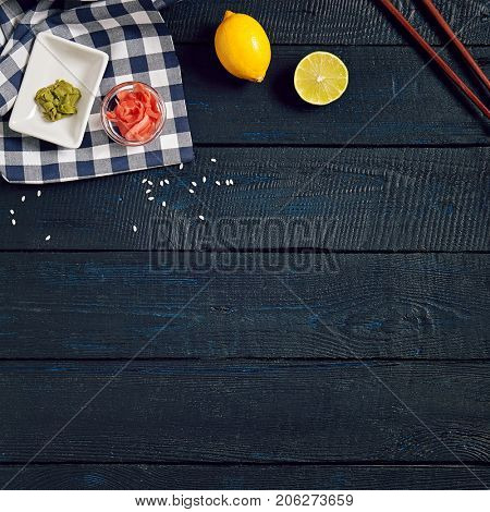 Japanese table setup with chopsticks and lemon with wasabi and ginger on dark wooden copyspace background